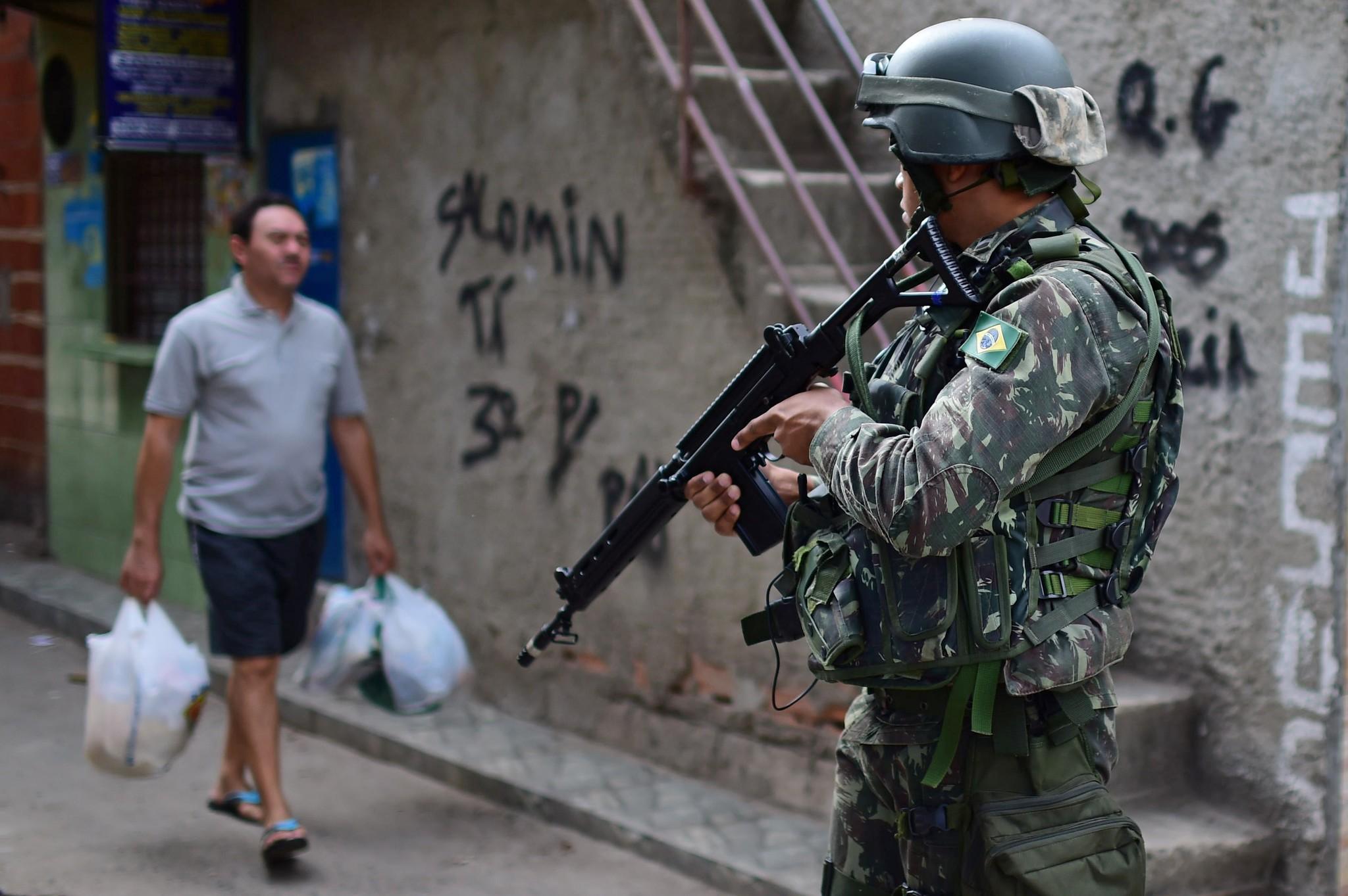 Brésil. Soldat avec armes et homme avec sacs de courses.